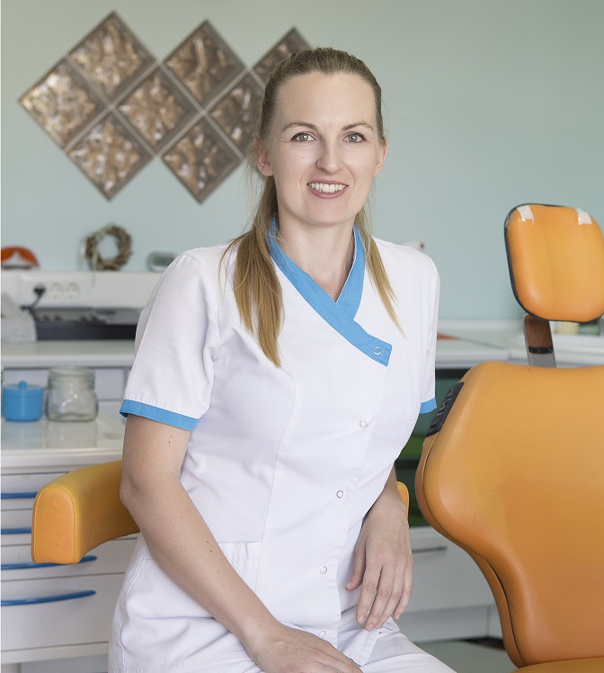Portrait image of the dental surgeon, Tatiana Fragou, sitting in her surgery.